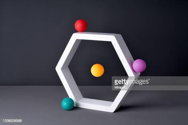 color spheres orbiting hexagon frame - orbiting stockfoto's en -beelden