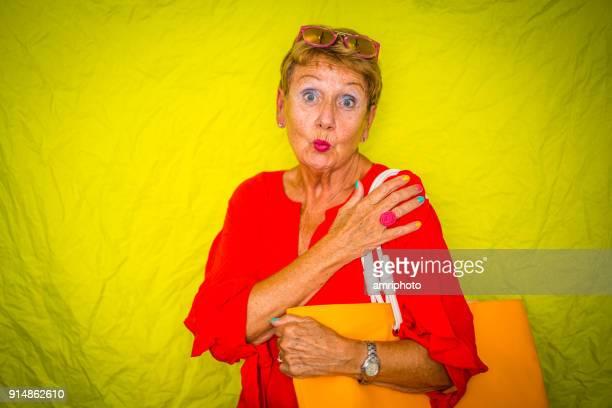 Kleur Surge voor stijlvolle senioren - 70 jaar oude vrouw maken van grappige kus mond gezicht