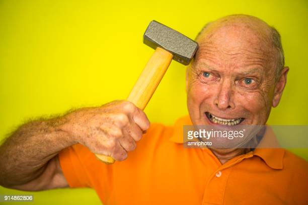 Color Surge for Stylish Seniors - 73 years old man with hammer on head and desperate face