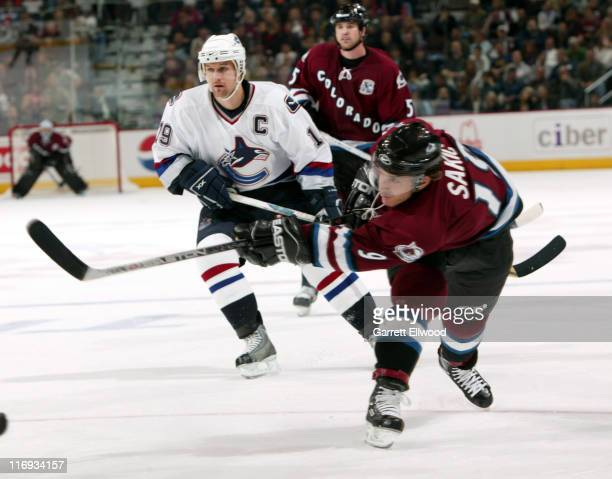 Colorado Avalanche center Joe Sakic takes a shot while Vancouver Canucks left wing Markus Naslund looks on during the game between the Vancouver...