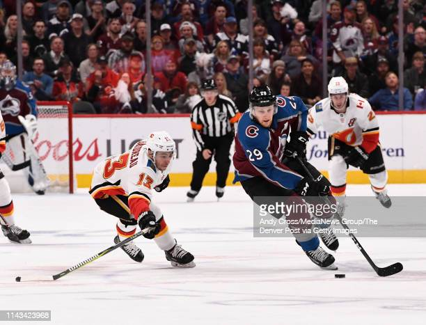 Colorado Avalanche center Nathan MacKinnon charges up ice against Calgary Flames left wing Johnny Gaudreau in the first period during the first round...
