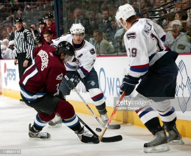 Colorado Avalanche defenseman Patrice Brisebois battles for control of the puck with Vancouver Canucks' center Brendan Morrison and left wing Markus...