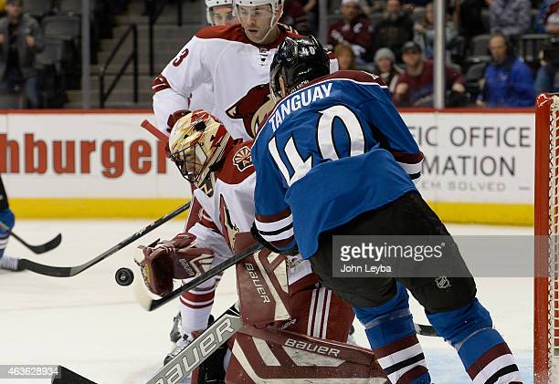 Colorado Avalanche left wing Alex Tanguay takes a swipe a the puck with this stick as Arizona Coyotes goalie Mike McKenna knocks it away during the...