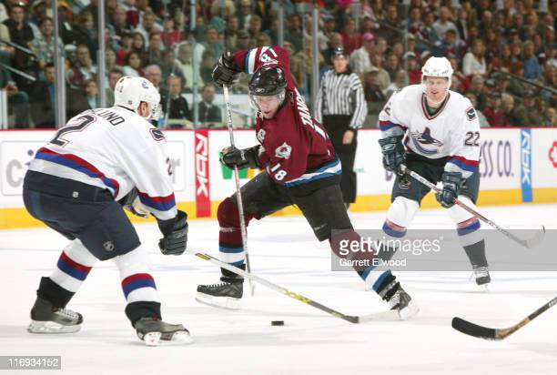 Colorado Avalanche left wing Alex Tanguay tries to take the puck past Vancouver Canucks defenseman Mattias Ohlund during the game between the...