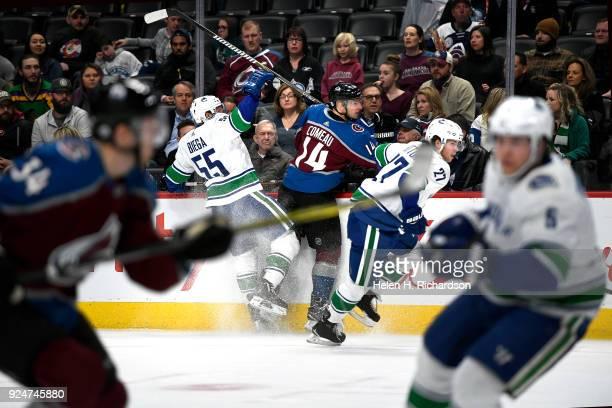 Colorado Avalanche left wing Blake Comeau #14 center gets hit against the glass by Vancouver Canucks' defensemen Alex Biega #55 Ben Hutton #27 right...
