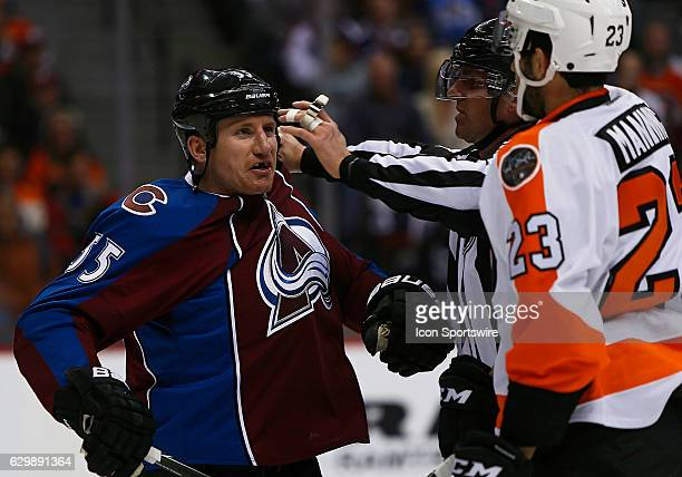 Colorado Avalanche left wing Cody McLeod and Philadelphia Flyers defenseman Brandon Manning mix words following a stoppage during a regular season...