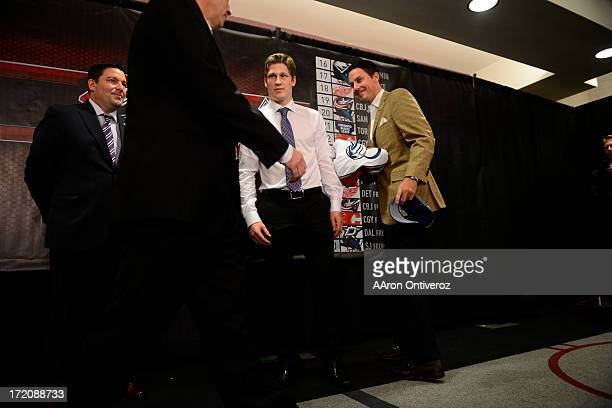 Colorado Avalanche rookie Nathan MacKinnon stands on stage with team president Josh Kronke during a press conference to welcome the number one...