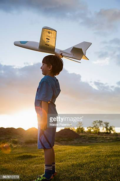 USA, Colorado, Boy (6-7) playing with model airplane outdoors