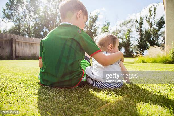 USA, Colorado, Brother (6-7) and sister (6-11months) sitting in grass