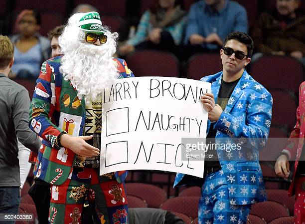 Colorado Buffaloes fans wearing Christmasthemed outfits hold a sign referring to head coach Larry Brown of the Southern Methodist Mustangs as the two...