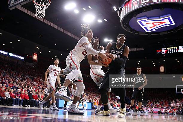 Colorado Buffaloes forward Tory Miller fights for the ball with Arizona Wildcats forward Keanu Pinder and guard Kobi Simmons during the first half of...