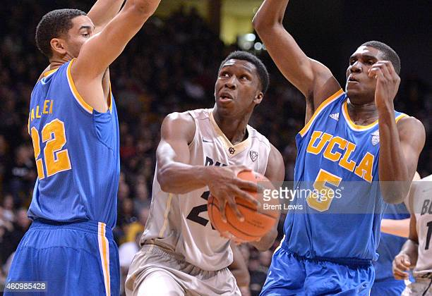 Colorado Buffaloes guard Jaron Hopkins looks for an opening to go for the shot around UCLA Bruins guard Noah Allen and UCLA Bruins forward Kevon...