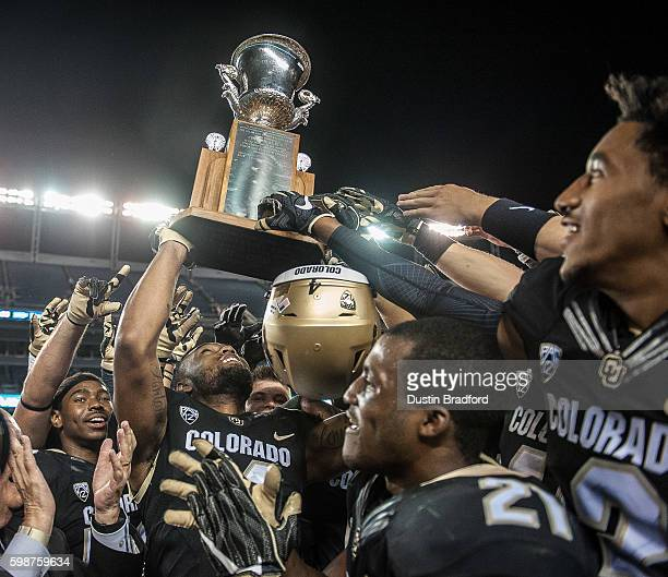 Colorado Buffaloes players celebrate as they hoist the Centennial Trophy after defeating the Colorado State Rams 447 at Sports Authority Field at...
