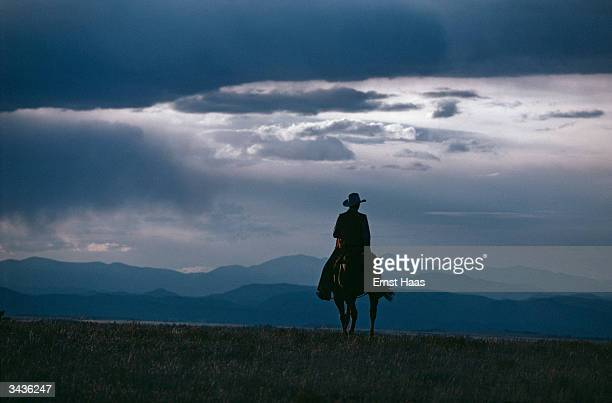 Colorado cowboy silhouetted against mountains and a lowering sky