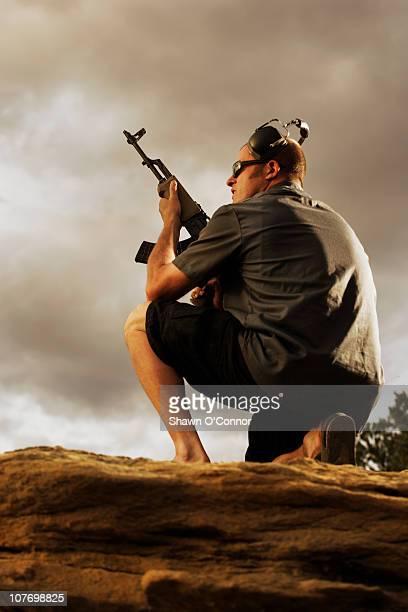 USA, Colorado, DeBeque, Man holding gun on rocks