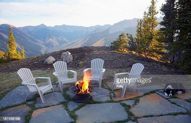 usa, colorado, dog lying down by fire pit and four empty chairs - fire pit stock pictures, royalty-free photos & images