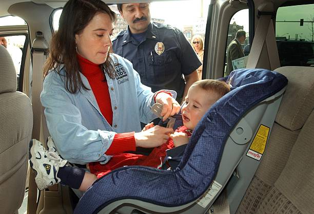 Colorado Fire Department Lieutenant Rick Nuanes Center Watches As Lisa VanBramer Places Her 18 Month Old Son Joshua Into A Carseat Part Of