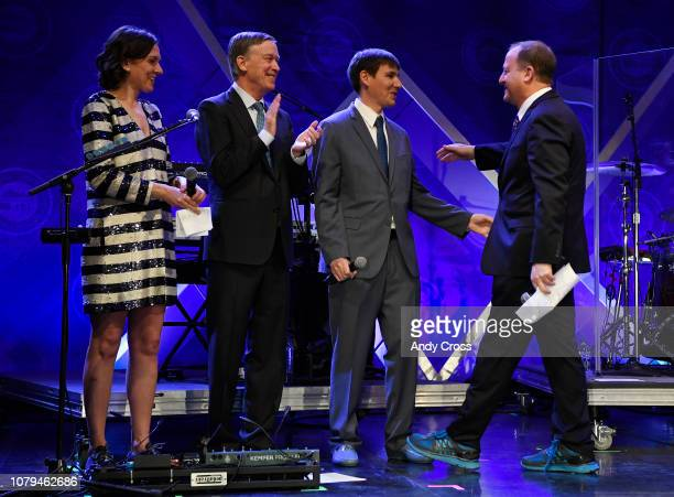 Colorado Gov Jared Polis right greets the First Gentleman of Colorado Marlon Reis third from right on stage as former Colorado Gov John Hickenlooper...