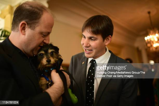 Colorado Governor Jared Polis left and First Gentleman Marlon Reis right meets 3 years old terrier Bruce at Governor's Mansion March 9 2019 First...