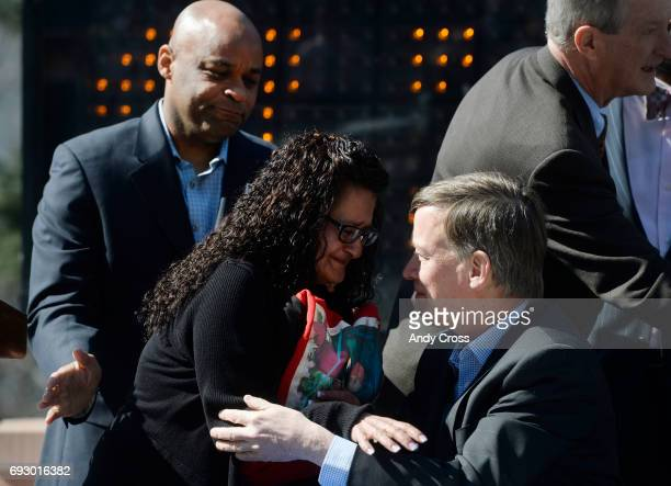Colorado Governor John Hickenlooper right comforts Linda Limon Medina left after signing HB141191 into law at the Colorado State Capital Tuesday...