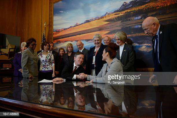 Colorado Governor John Hickenlooper shacks the hand of Karina Vargas right who was paralyzed from a shooting outside Aurora Central High School after...