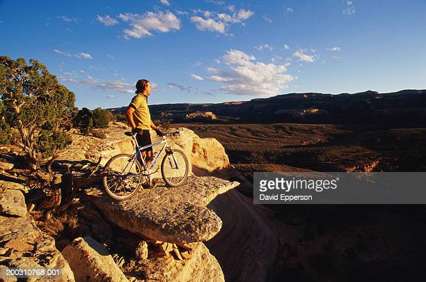 usa, colorado, grand junction, man with mountain bike above canyon - david cliff stock pictures, royalty-free photos & images