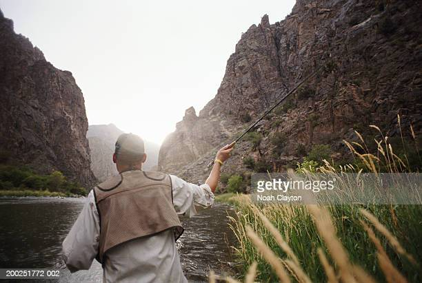 usa, colorado, gunnison, man fly fishing, rear view - fly casting stock pictures, royalty-free photos & images