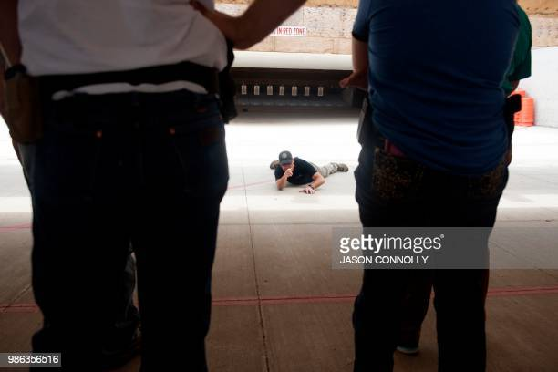 Colorado instructor Paul Gregory demonstrates to school teachers and administrators how to fire a gun from a prone position during a three day...
