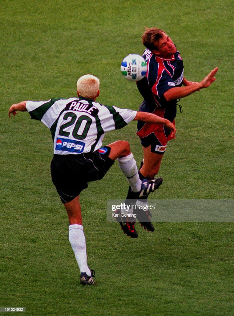 Colorado midfielder Ross Paule attempted to defend against a header from New England 's Ivan McKinley in the first half of MLS action in Denver Saturday July 11, 1998. : News Photo