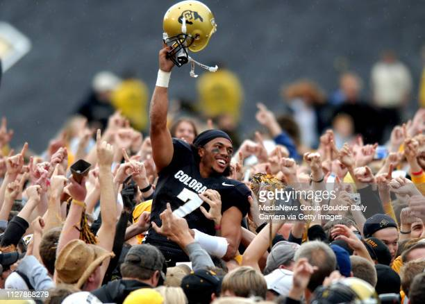 Colorado QB Bernard Jackson is lifted above the crowd by fans celebrating CU's first victory of the season