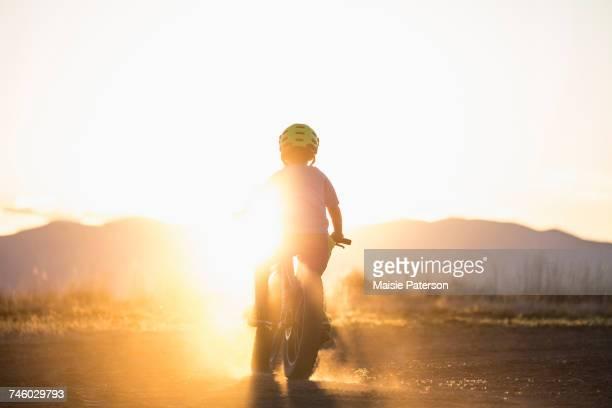 USA, Colorado, Rear view of boy (8-9) cycling at sunset