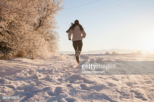 USA, Colorado, Rear view of female runner on dirt road