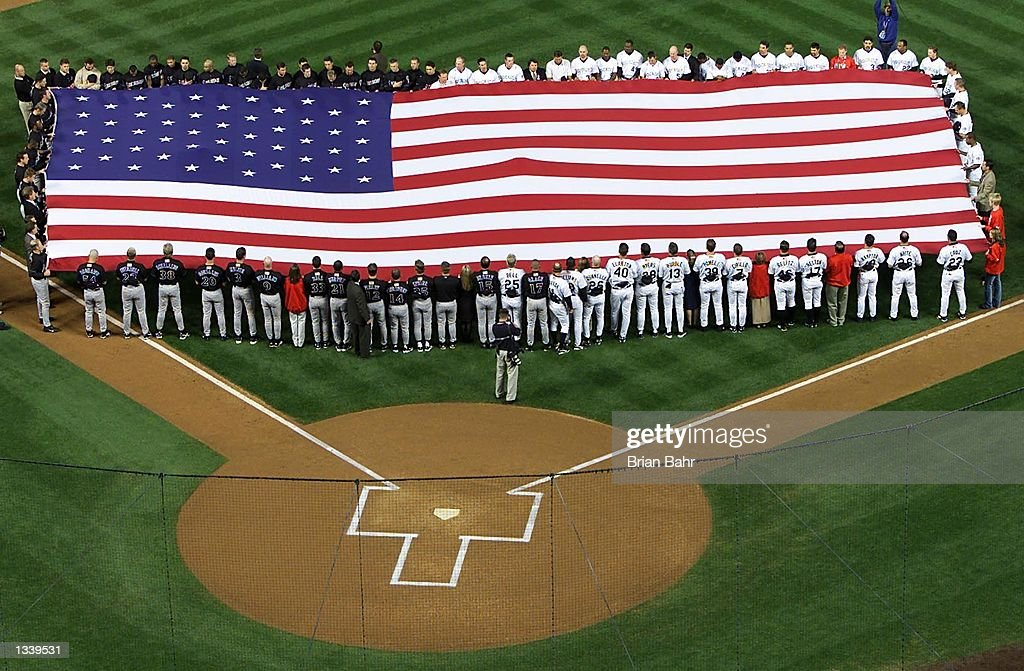 Colorado Rockies and Arizona Diamondbacks baseball players hold a large U.S. flag together during 'God Bless America' and the 'Star Spangled Banner' musical anthems before the start of their game at Coors Field September 17, 2001 in Denver, Colorado.