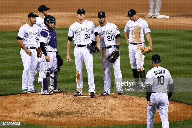 Colorado Rockies catcher Tony Wolters and Colorado Rockies left fielder Ian Desmond stand with Colorado Rockies starting pitcher Jeff Hoffman on the...