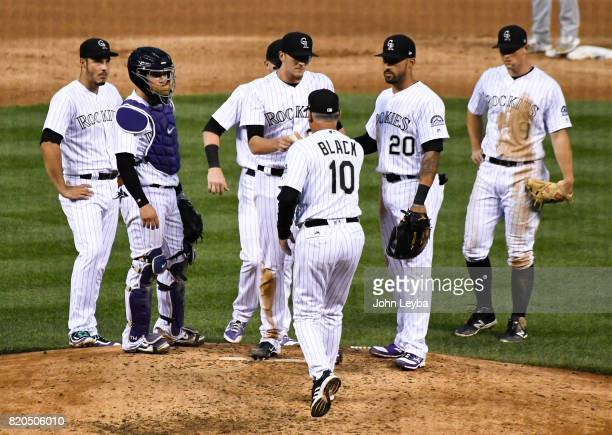 Colorado Rockies catcher Tony Wolters and Colorado Rockies left fielder Ian Desmond stand with Colorado Rockies starting pitcher Jeff Hoffman gives...