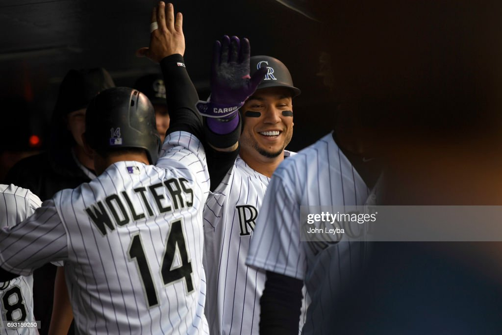 Colorado Rockies catcher Tony Wolters (14) and Colorado Rockies right fielder Carlos Gonzalez (5) high five with smiles in the dugout after scoring on a double by Colorado Rockies starting pitcher Antonio Senzatela (49) in the second inning on June 6, 2017 in Denver, Colorado at Coors Field. Senzatela had a 3 run RBI on the play.
