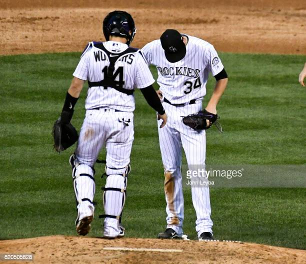 Colorado Rockies catcher Tony Wolters stands with Colorado Rockies starting pitcher Jeff Hoffman as he bows his head after giving up a single to...
