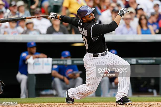 Colorado Rockies catcher Wilin Rosario hits a double against the Chicago Cubs at Coors Field on August 7 2014 in Denver Colorado The Chicago Cubs...