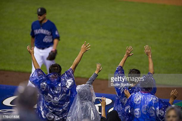 Colorado Rockies fans wearing purple ponchos cheer as Jhoulys Chacin of the Colorado Rockies walks into the dugout after a scoreless sixth inning of...