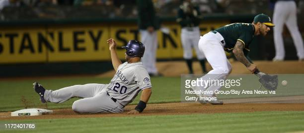 Colorado Rockies first baseman Wilin Rosario is safe as Oakland Athletics third baseman Brett Lawrie takes the throw after a single by Colorado...