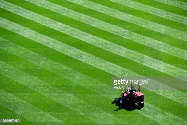Colorado Rockies groundskeeper Adam Steward carefully guides the riding mower in the outfield at Coors Field before the game agains the New York Mets...