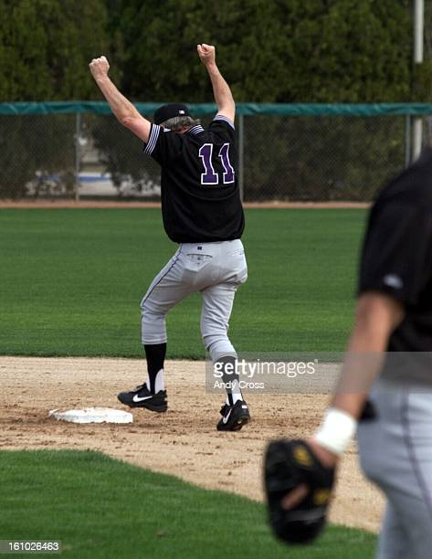 Colorado Rockies head coach Jim Leyland raises his arms up in victory as he reached second base without being tagged out during 'pickle' practice...