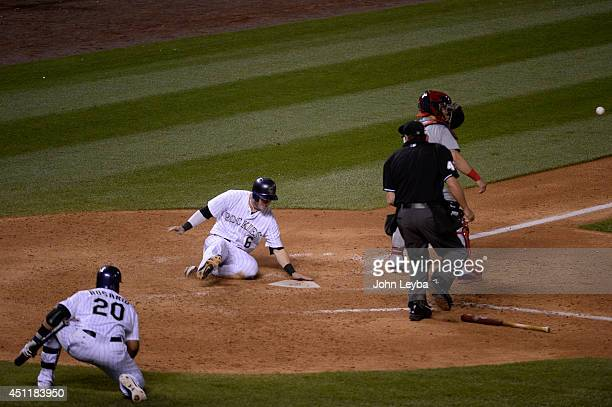 Colorado Rockies left fielder Corey Dickerson slides at home plate safe on a hit by Colorado Rockies first baseman Justin Morneau in the seventh...