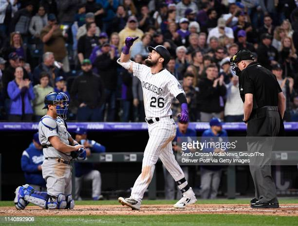 Colorado Rockies left fielder David Dahl points to the sky at home plate in front of Los Angeles Dodgers catcher Austin Barnes after hitting a solo...
