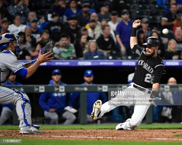 Colorado Rockies left fielder David Dahl slides into home plate against Toronto Blue Jays catcher Luke Maile , but not ahead of the throw, ending the...