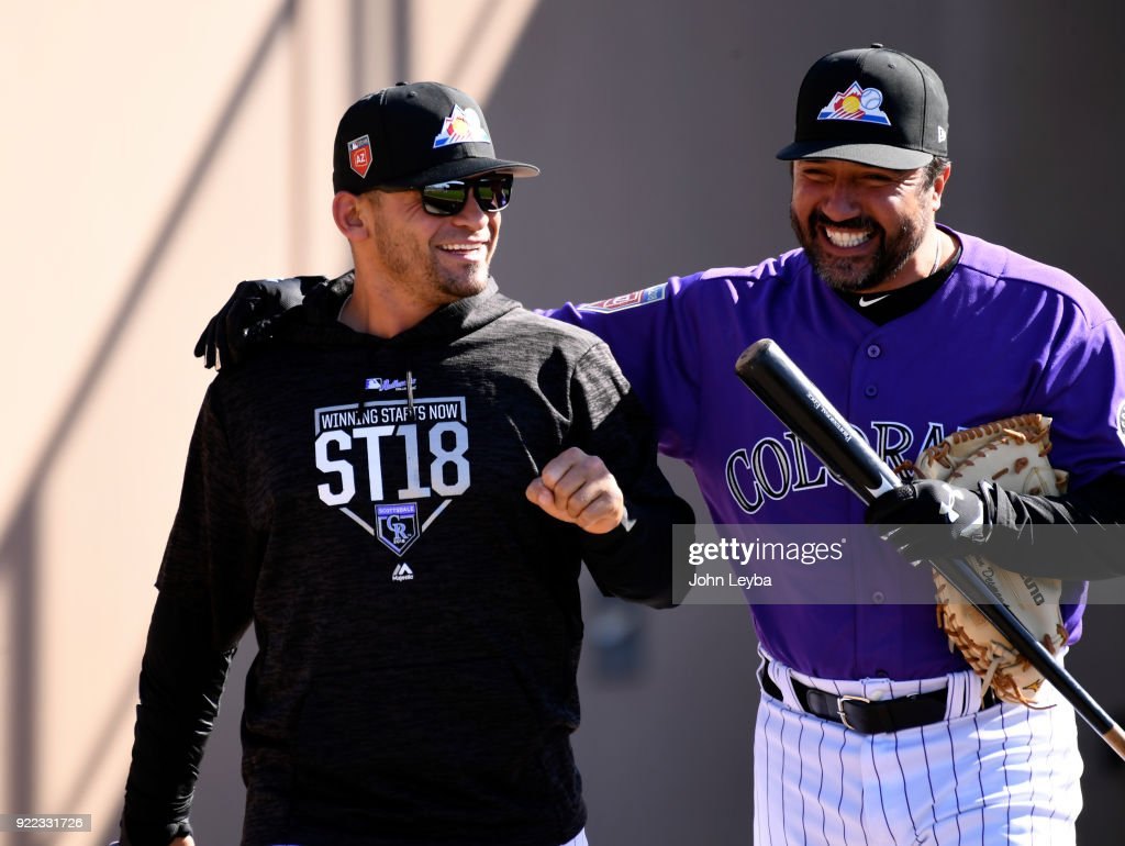 Colorado Rockies left fielder Gerardo Parra (8) and Vinny Castilla (9) laugh as they head to the the backfield during workouts on February 21, 2018 at Salt River Fields at Talking Stick in Scottsdale, Arizona.