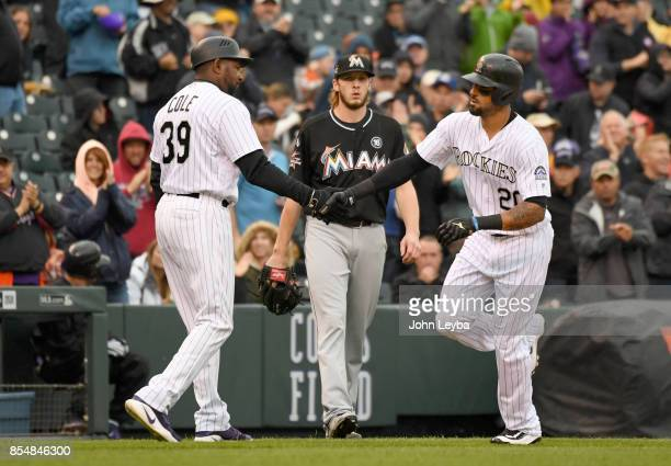 Colorado Rockies left fielder Ian Desmond shakes hands with third base coach Stu Cole after hitting his 7th homer to right center in the second...