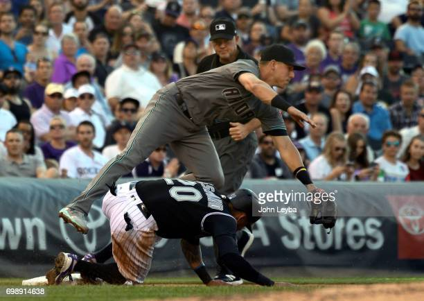 Colorado Rockies left fielder Ian Desmond slides in at third base safe on a throwing error by Arizona Diamondbacks catcher Jeff Mathis during the...