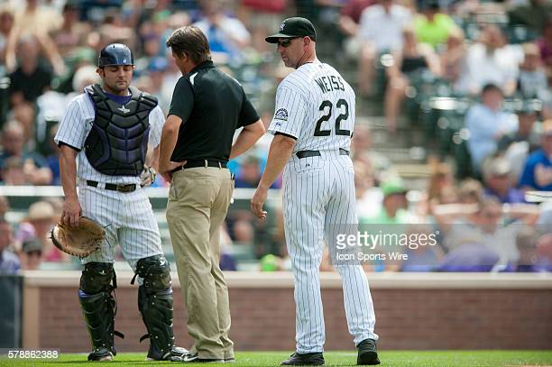 Colorado Rockies manager Walt Weiss and Rockies trainer Keith Duggar visit with catcher Michael McKenry during a regular season Major League Baseball...