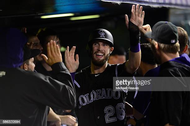 Colorado Rockies outfielder David Dahl high fives his teammates after scoring in the eighth inning during the game against the Miami Marlins at Coors...
